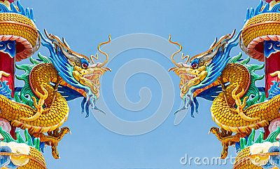 Double statue d or de dragon sur le fond de ciel bleu