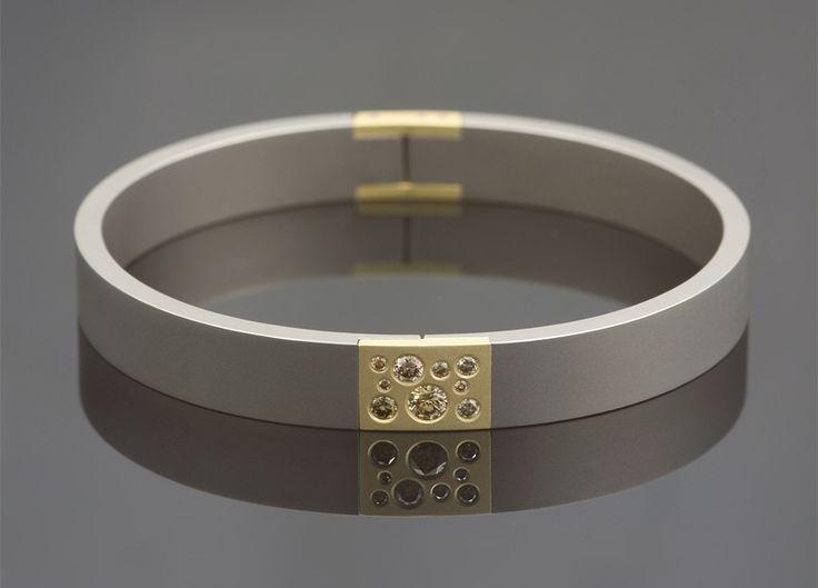 Armband van Marc Lange, titanium gecombineerd met geelgoud, bezet met bruine diamanten.