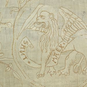 """Switzerland, 1550-1600 Design of foliated scrolls and roundels with the symbols of the four apostles. One roundel shows a lion and the words: """"Sant Mark."""" Two other roundels (incomplete) show portions of the Eagle (St. Mathew) and Ox (St. Luke). A very small part of a brown and white fringe remains at the bottom."""