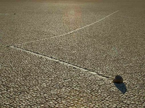 Racetrack Playa in Death Valley California: Scattered about the desert are large rocks with mysterious trails left behind them. The trails show that these rocks have rolled and zig-zagged across the ground, sometimes for as long as 860 feet. Yet no one has ever seen the stones actually move. The trails last for years before fading, so it is almost impossible to predict when the stones will move or how fast they move.