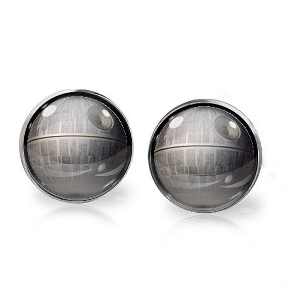 This listing is for ONE pair of Death Star stud earrings inspired by Star Wars. A perfect gift for the fangirl in your life!   These earrings measure 14mm in diameter and utilise glass domes to magnify high quality images set beneath. They are made using high quality surgical steel ear posts for sensitive ears. This listing is part of our Buy THREE get ONE free promotion. Purchase any three pairs of earrings in the promotion and receive one pair of your choice free. Please DO NOT add the…