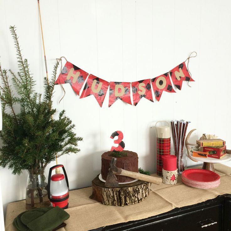 My sons lumberjack themed 3rd birthday! We used fresh greenery and cut a piece of log for the cake stand! The plaid thermos was my mothers and the antlers were from a buck my dad shot years ago! The amo is over years 70 years old and was from my great grandfathers gun shop! I loved being able to use things that we already own and treasures from my grandmas house, this keeps the cost down and holds special meaning!! Hudson loved his party complete with actual wood chopping on the front…