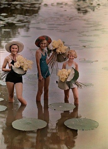 Girls standing in water holding bunches of American Lotus, Amana, Iowa, 1938. Photograph by J. Baylor Roberts.