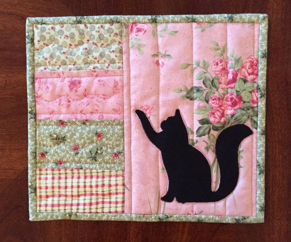 This pretty mug rug has a Victorian look to it. The cat silhouette was appliqued on and then it was machine quilted. The double fold binding was machine sewn to the front and then hand stitched to the back for a clean neat finish. It has two layers of Warm and Natural batting to protect your surfaces. The measurements are 8 by 9.5. It was made in a smoke free home.