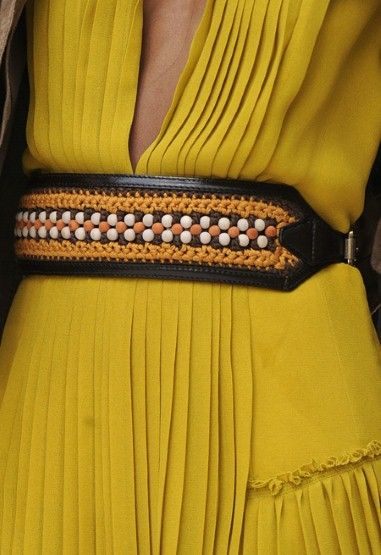 A mustard-toned pleated dress at Burberry was cinched with a woven, artisanal cummerbund.