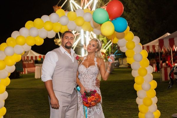 CJ Lana Perry and Miroslav Rusev Barnyashev under balloon arch yellow white at wedding outdoor