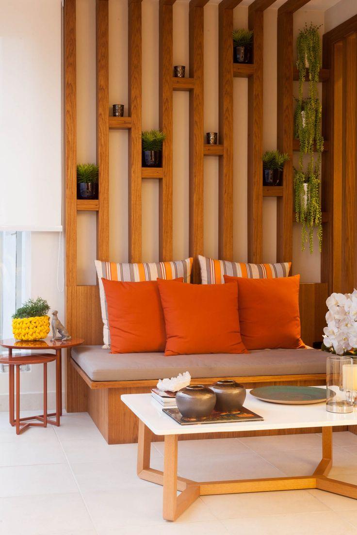 Vem ver a decoração desse apartamento em SP. Na varanda, espaço para relaxar com painel de madeira ripado, futton e vasos na parede.