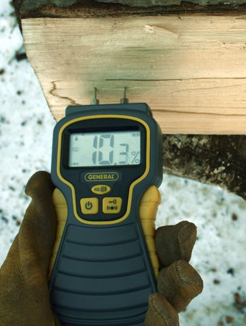 Using a moisture meter to test the dryness of firewood.