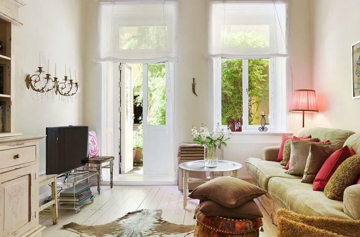 гостиная выход на террасу диван светлый пол шкура столик подушки телевизор