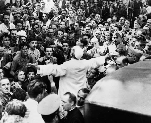 August 13,1943:   AMERICAN AIR RAID. ITALY  -   Men, women and soldiers gather around Pope Pius XII, his arms outstretched, on Oct. 15, 1943, during his inspection tour of Rome, Italy, after the Aug. 13 American air raid in World War II.