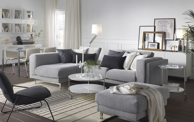 A light living room furnished with a light gray two-seat sofa combined with a chaise lounge. Shown together with a round coffee table on castors and a light gray footstool.