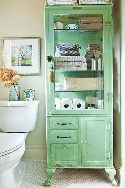 A salvaged apothecary cabinet in a classic color adds charm—and savvy storage—to a small bathroom. | Photo: Erica George Dines