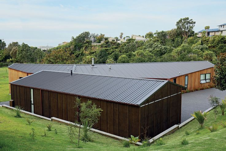 The dark-stained gaboon plywood of the guest wing and garage contrasts the home's western red cedar cladding.