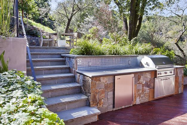 The multilevel deck features a hot tub, outdoor kitchen and beautiful hillside landscaping with a miniature waterfall fountain. Photo: OpenHomesPhotography.com / SF
