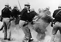 血の日曜日事件 (1965年) - Wikipedia   1965年の血の日曜日事件(ちのにちようびじけん)は、1965年3月7日に、アメリカの公民権運動中にアラバマ州の都市セルマで起きた流血事件。  経過編集  詳細は「アフリカ系アメリカ人公民権運動」を参照 1965年3月7日、525から600名ほどの公民権運動家達がセルマを出発する。セルマの人口の半数ほどの黒人達は、差別と脅迫により有権者登録を妨害された。同じ年の2月18日に、公民権運動のデモ中に警察官からの暴力から喫茶店に避難していた両親を守ろうとした黒人、ジミー・リー・ジャクソンを警察官が銃撃。ジャクソンは8日後の2月26日に感染症のため病院で死亡した。  3月7日のデモ隊は、州都モンゴメリーまで行進を続けることで、警官隊達が合衆国憲法違反をしたことをアピールしようとした。キング牧師がセルマからモンゴメリーへのデモを組織したのは有権者登録をした黒人達を知事に保護させようとしたためである。…