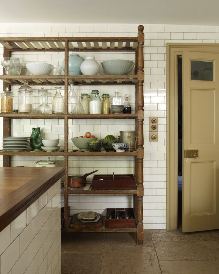 Old White subway tile to ceiling, grey grout, and beautiful worn coffee-colored stone floor.  Shelves