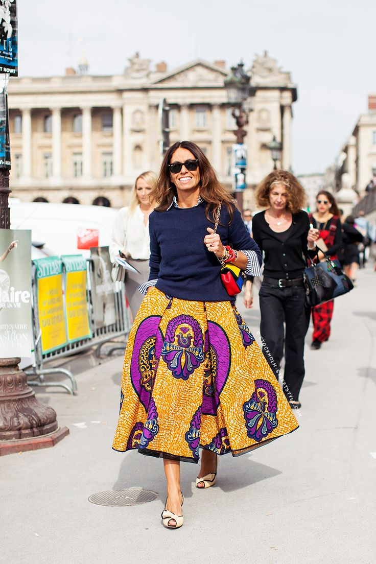 Viviana Volpicella in a purple and yellow batik flare skirt, and navy blue crewneck sweater.
