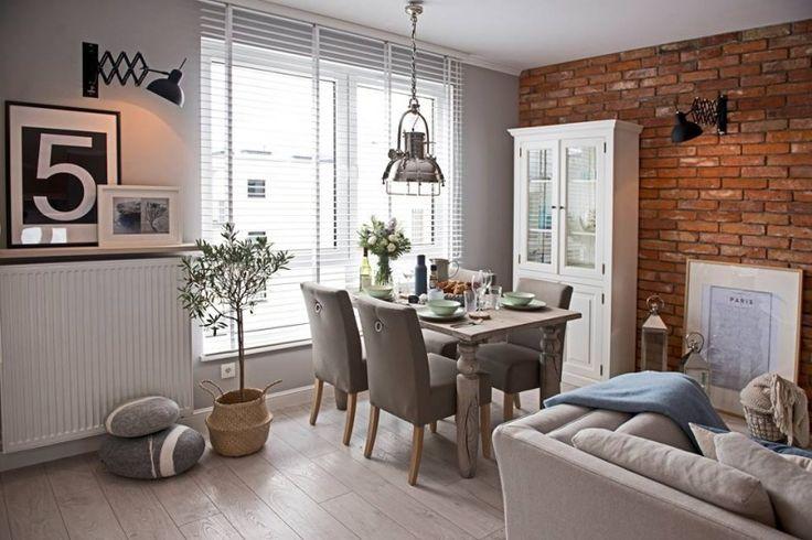 Aranżacja jadalni połączonej w salonie, którą wzbogacono czerwonymi cegłami na ścianie. Charakterystyczna lampa o...