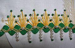 Sur ce site on peut voir plusieurs broderies sur lesquelles ont été ajoutées des perles nacrées ou des perles de verre, parfois même les deux en même temps.  Très beau.