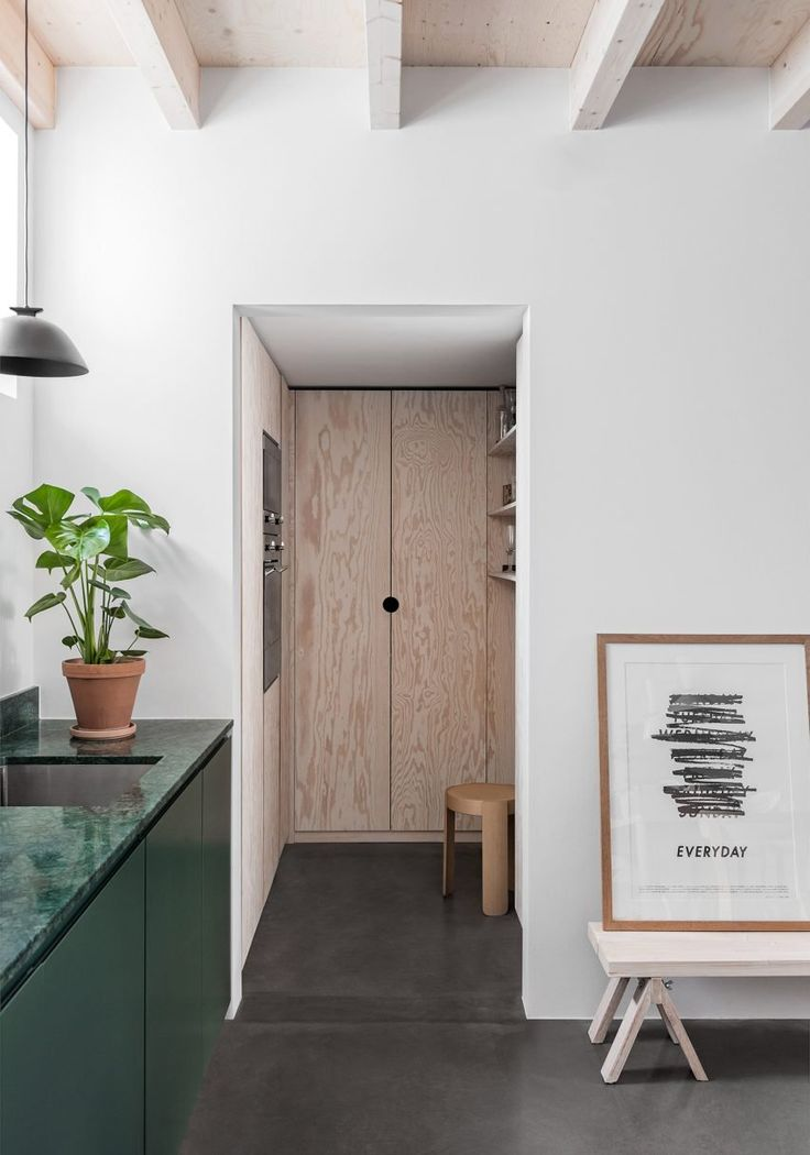 The wooden beams of the new floor are left exposed in this house and are offset by a series of neutral finishes like white-washed wood, white-painted walls and concrete floors, which create a backdrop for the family to display its collection of design objects and plants.