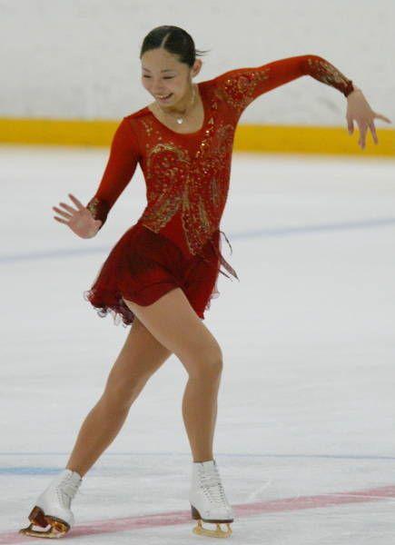 フィギュアスケートの全日本選手権最終日は2003年12月27日、長野市のビッグハットで行われ、女子で16歳の安藤美姫(オリオンク、愛知・中京大中京高校1年生)が女子で大会初の4回転ジャンプに成功し、初優勝を飾った。  前日のショートプログラム(SP)で2位につけた安藤は、この日のフリーで1位となって逆転。先のグランプリ(GP)ファイナルで優勝した村主章枝(新横浜プリンスク)、GPファイナル3位の荒川静香(早大)ら有力選手を抑え、新女王の座に就いた。  写真は、4回転ジャンプを決めた直後、思わず笑顔を見せる女子優勝の安藤美姫 【時事通信社】