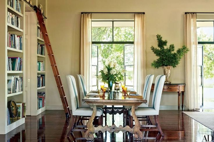 In the dining area, a French farmhouse table is flanked by Rose Tarlow Melrose House chairs cushioned in a custom-made Peter Fasano linen; the ladder is by the Putnam Rolling Ladder Co.