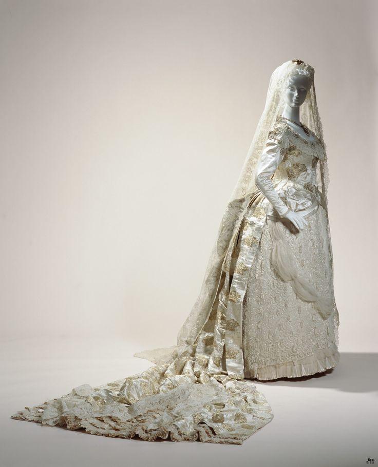 1882г., Англия  Это роскошное платье из шелковой парчи демонстрирует последние модные тенденции своего времени в стилистике турнюра. Изысканные драпировки и защипы, украшенные кружевами, оборками, вышивкой. Не менее потрясающий шлейф длинной 2,4 метра показывает, что невеста была женщиной из высшего света. Традиционно, свадебные платья на Западе не были ограничены в использовании цвета, и невесты носили просто великолепные, модные наряды.