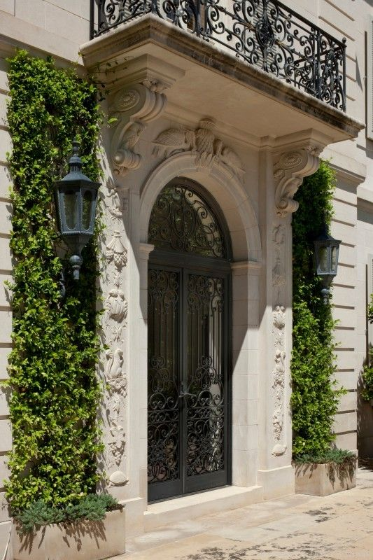 Beautiful wrought iron door with classical stone surround for Balcony surrounds