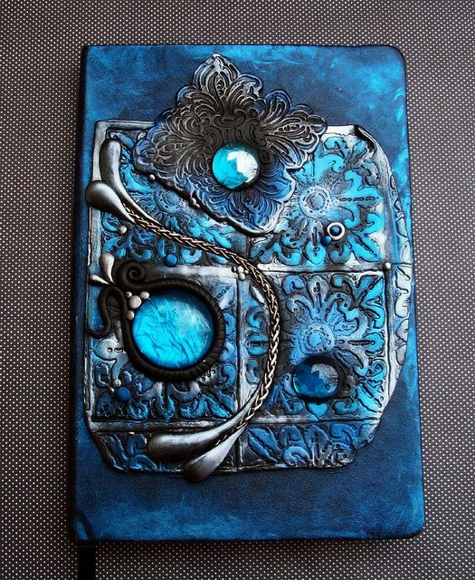 This is a blank journal that I hand painted and decorated with a polymer clay piece of my own design. All of that wonderful shimmery blue comes from powdered pigments. Included are glass gems and a bit of chain