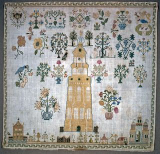 Within an acorn border, isolated motifs with a town at the bottom dominated by a large yellow tower.  Netherlands lion in a Holland garden, symbol of the United Provinces, at upper right.  Coat of arms of Middelburg at upper left. Unfinished