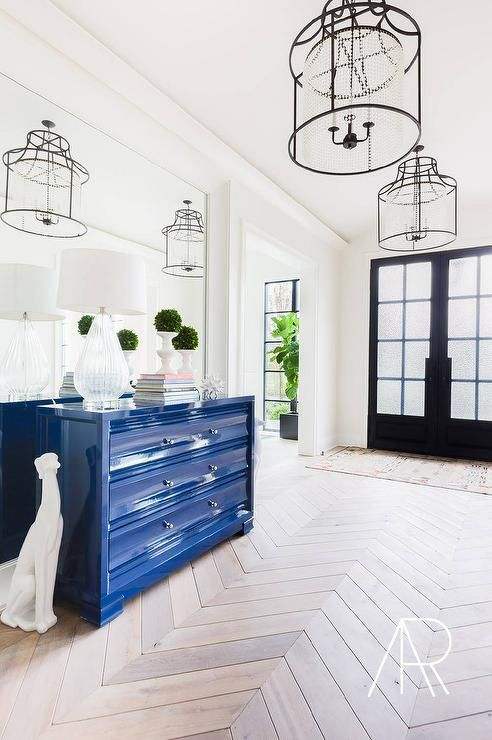 Redo Your House - Amazing foyer features iron lanterns accented with clear beading illuminating a glossy blue lacquer chest of drawers flanked by white dalmatian statues lining a mirrored accent wall atop a wood herringbone floor.