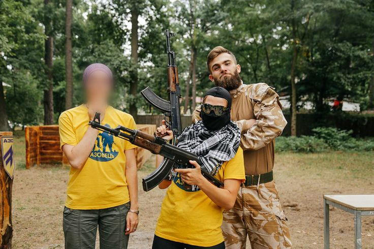 Young Azov Battalion trainee poses with Kalashnikov rifles in front of his instructor at a training camp near Kiev [900x600]