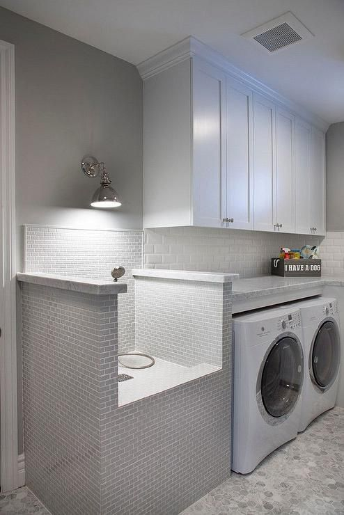 White and gray laundry room features white cabinets painted Sherwin Williams Pure White paired with gray marble countertops and a white mini brick beveled tile backsplash.