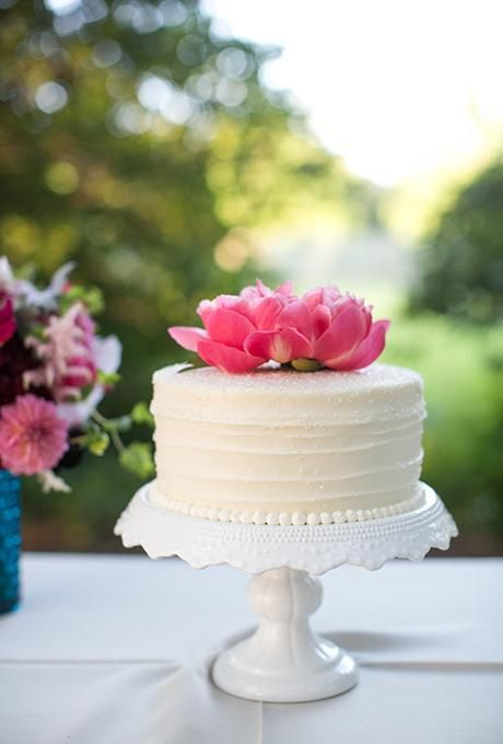 A one-tiered white wedding cake topped with fresh flowers