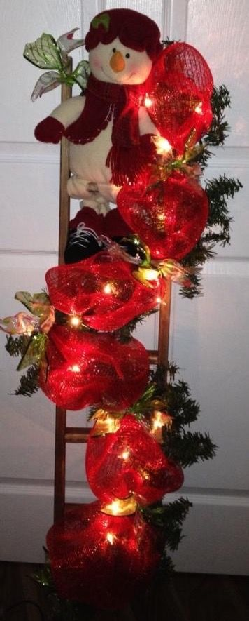 snowman on ladder with lighted mesh garland