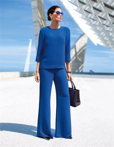 Weite, weich fließende Hose, Große Damen Business-Tasche aus echtem Leder mit Bodenfüßen, Schlichte Pumps aus Lackleder mit hohem Absatz, Schlichtes Blusentop mit verlängertem Rückteil