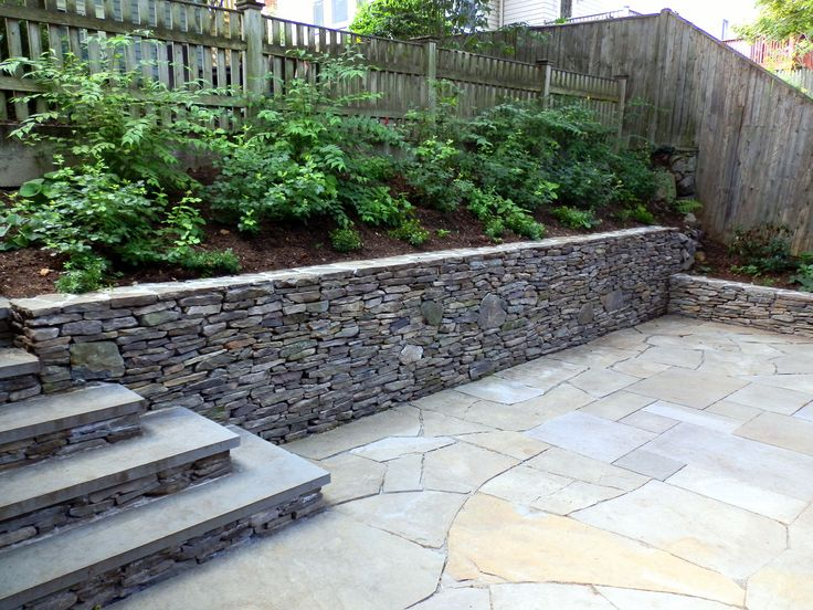 Flagstone Courtyard Area With Staircase On Stone Retaining Wall.