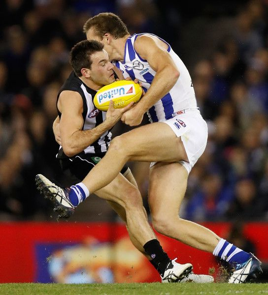 Levi Greenwood of the Magpies is tackled by Drew Petrie of the Kangaroos during the 2016 AFL Round 18 match between the Collingwood Magpies and the North Melbourne Kangaroos at Etihad Stadium on July 22, 2016 in Melbourne, Australia.