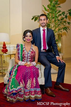 An Indian bride and groom celebrate their wedding reception after their traditional Sikh ceremony. The bride dons a colorful halter lengha and the decor has a gold and pink color palette.