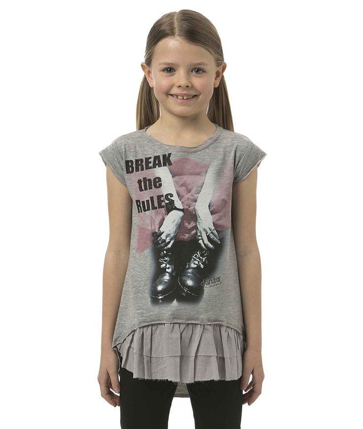 T-shirt in jersey stretch leggero, con taglio asimmetrico più lungo sul retro e arricchito da rouches sulla schiena; la grafica che invita a rompere gli schemi ne fa un capo di forte carattere e personalità.