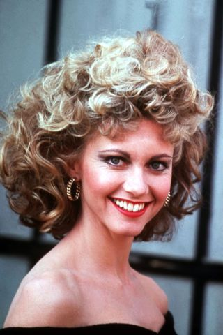 Olivia Newton-John starring in Grease. A look back at the permanent waves and curls that dominated classic movies and concert stages in the '70s, '80s and '90s here.