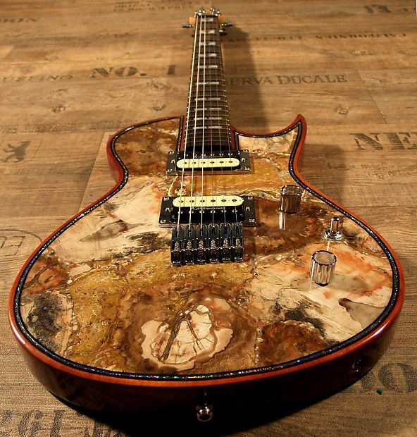 """Today I proudly offer you something absolutely crazy.Something the world has not seen yet.I have built this Zerberus-Guitars Chronos with a top made of REAL PETRIFIED WOOD.This is no fake...no airbrush....no foto-finish....no plastic material.....It is a real 0.2"""" top of petrified wood (around 250.000.000 Years old).And still that guitar is only around 8lb and not heavier than most standard wooden guitars.  IMAGINE: You could be the first lucky devil in the whole world who owns   and plays"""