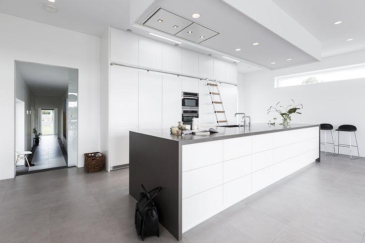 Det er muligt at udnytte pladsen i køkkenet optimalt med skabe hele vejen fra gulv til loft. Den smarte stigeløsning gør det brugervenligt at nå hurtigt og sikkert op til øverste hylde. Hvide køkkenelementer kan brydes elegant ved at vælge klinker og bordplade i en anden farve, f.eks. grå.