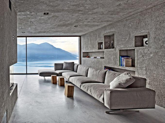Odkládací a úložný prostor za pohovkou je řešen vestavěnými nikami v hrubé stěně z vymývaného betonu, která kontrastuje s hladkou a lehce udržovatelnou betonovou podlahou