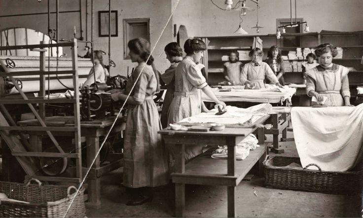 Interieur van de strijkafdeling van een wasserij. Vrouwen werken aan een mangelmachine of staan te strijken met strijkbouten die nog niet elektrisch zijn. [Amsterdam], 1914.