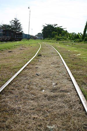 遠くには線路を歩く人、朽ち果てた貨車。レールは草に埋もれながらも鈍く光っているけれど、本当に列車が来るのかは分からない。2004/9 カンボジア王立鉄道 Royal Railways of Cambodia プノンペン駅 Phnom Penh Station(カンボジア王国 Kingdom of Cambodia)© 2010 風旅記(M.M.) 風旅記以外への転載はできません...