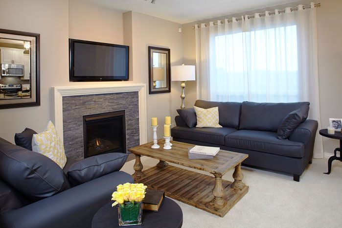 Living room with wall centred fireplace in the Orion II showhome in King's Heights in Airdrie by Shane Homes.