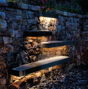 LED striplights are tucked on the underside of cantilevered flagstone slabs to illuminate this waterfall feature in a garden.