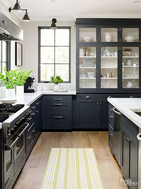 Dark kitchen cabinets with marble countertops and hutch designed to look like an antique apothecary cabinet.