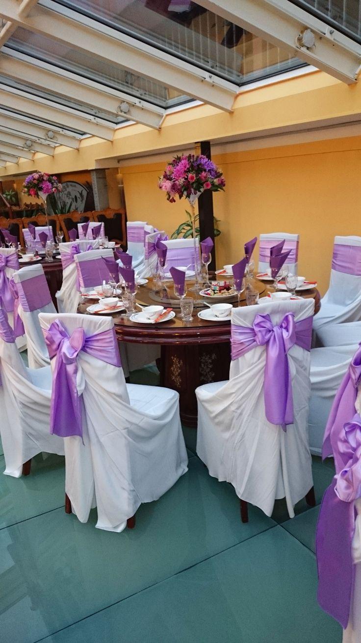 Pink és lila esküvői asztaldísz magas, vékony vázában. Színben passzol a székszoknya masnijához.